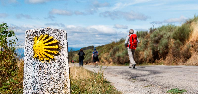 peregrinos haciendo el camino de santiago con mojon